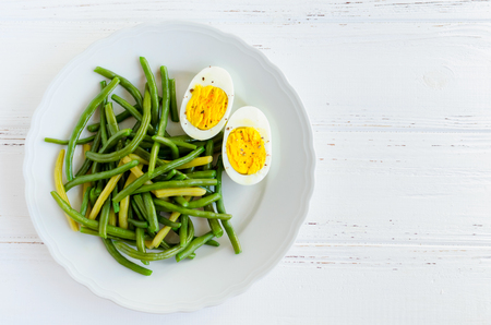 Cooked green beans with boiled eggs in white plate on wooden background with space for text. Healthy vegetarian food concept. Top view. Copy space. Stock Photo