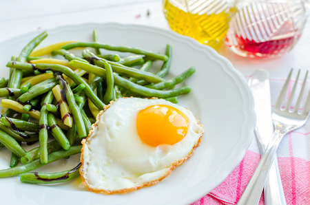 Cooked green beans with sauce balsamico glassa and fried egg in white plate on wooden background with red napkin, knife and fork. Healthy eating. Vegetarian food concept. Stock Photo
