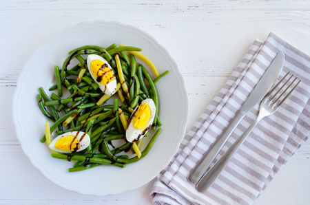 Warm salad with cooked green beans with boiled eggs and sauce balsamico glassa in white plate on wooden background with grey napkin, knife and fork. Healthy eating. Vegetarian food concept. Top view.