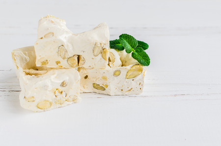 Delicious traditional Italian festive torrone or nougat with nuts on white wooden background with place for text. Soft nougat blocks with almonds with fresh mint leaves. Italian sweets. Copy space. Stock fotó