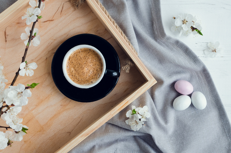 Cup of coffee espresso, colorful chocolate eggs and cherry blossom on wooden tray on white shabby chic table with gray tablecloth. Easter treats concept. Top view.