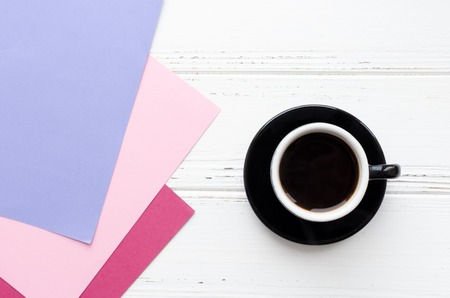 Cup of black coffee and pink, purple and magenta paper texture on white wooden table. Coffee break when choosing color stylish scheme in home interior. Harmonious and beautiful combination. Top view.