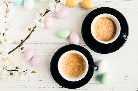 Two cups of coffee espresso, colorful chocolate eggs and cherry blossom on white shabby chic background. Easter treats concept. Top view.