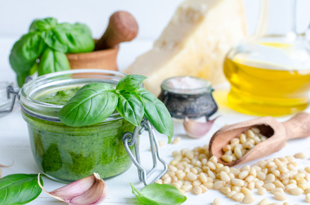 Pesto genovese - traditional Italian green basil sauce with raw ingredients on white wooden background. Basil leaves in mortar, Parmesan cheese, pine nuts, olive oil, garlic and salt. Standard-Bild