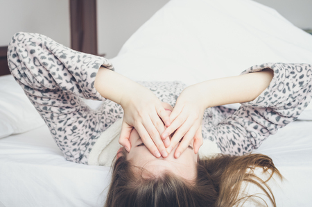Young woman covers her eyes with hands lying on the bed in the morning. Student or schoolgirl do not want to wake up early for school or univercity. Oversleep, not getting enough sleep concept. Foto de archivo