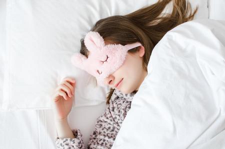 Schöne junge Frau in der niedlichen Schlafmaske und im warmen Pyjama, die im Bett liegen und am Morgen schlafen. Draufsicht. Speicherplatz kopieren. Standard-Bild