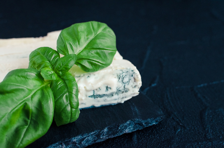 Gorgonzola cheese with mascarpone with basil on slate plate on dark background with place for text. Tasty appetizers. Copy space.