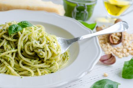 Spaghetti with homemade pesto sauce on white wooden table. Pasta with pesto alla genovese. Italian cuisine concept.
