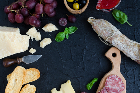 Table full of mediterranean appetizers, tapas or antipasti. Assorted Italian style banquet food set. Delicious snack on party. Empty place for your text in the middle. Top view. Copy space.
