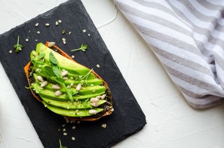 Healthy avocado toasts on sweet potato for breakfast or lunch with vegan pesto, microgreens, sliced avocado, hemp and sunflower seeds. Vegetarian food. Clean eating. Top view. Copy space.