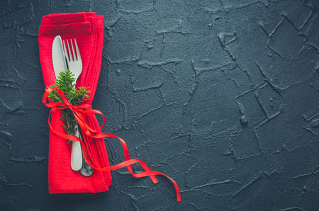 Christmas and New Year holiday celebration table setting on black background. Place setting for Christmas Dinner with red napkin and natural decorations. Decor. Top view. Copy space. Stock Photo