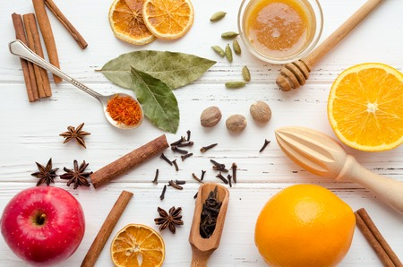 Christmas spices and ingredients for mulled wine or gluhwein with orange, cinnamon sticks and anise on white wooden background. Spicy warm beverage. Seasonal mulled drink. Top view.