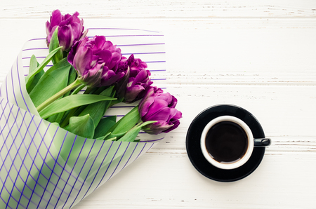 Cup of coffee with bouquet of purple tulips on white shabby chic