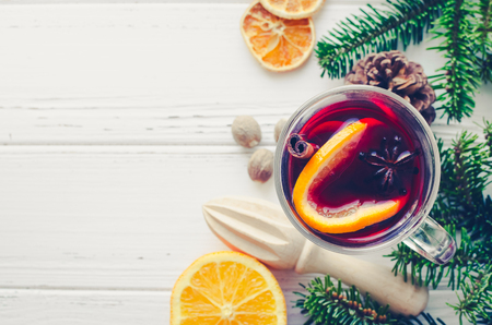 Hot red mulled wine in glass with orange, cinnamon sticks and star anise with ingredients on white wooden background. Spicy warm beverage. Seasonal Christmas mulled drink. Copy space. Top view. Stock Photo