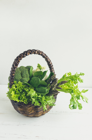 Assorted green vegetables in a basket on white wooden background with place for text. Fresh veggies and greens: spinach, fennel, celery, lettuce, asparagus and broccoli. Copy space. 스톡 콘텐츠