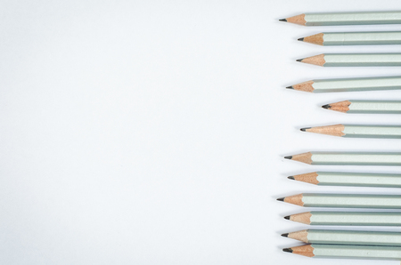 Wooden silver pencils on empty white paper. Minimalist template with copy space by top view close up macro.
