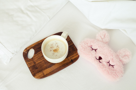 Cup of coffee with cute pink sleep mask on the bed on cozy lazy sunday. White bedding sheet, blanket and pillows. Good morning concept. Enjoy slow life. Top view.