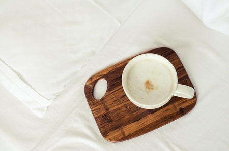 Cup of coffee cappuccino on wooden board on a bed on cozy lazy sunday. White bedding sheet, blanket and pillows. Good morning concept. Enjoy slow life. Top view.