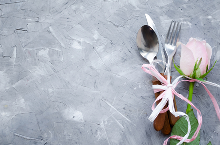 Valentine's Day romantic table setting with pastel pink rose and cutlery on grey