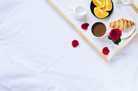 Romantic Valentines Day breakfast in bed, tray with fresh croissant, cup of coffee espresso with milk, fresh oranges and red rose. Stock Photo