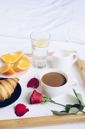 Romantic Valentines Day breakfast in bed, tray with croissant, cup of coffee espresso with milk, fresh oranges, glass of water with lemon and red rose.