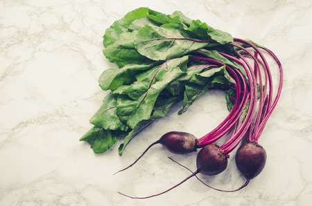 Bunch of homegrown organic young beets with green leaves on the table. Fresh harvested beetroots on white marble background. Top view. Reklamní fotografie