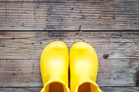 Yellow children`s rain rubber boots on wooden background. Top view. Copy space.