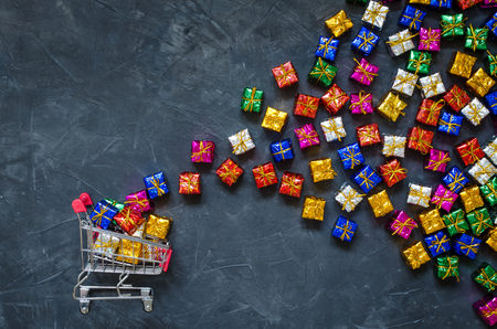Small shopping cart with presents on black background. Trolley from a supermarket full of colorful gift boxes. Online shopping concept Black Friday and Ciber Monday. Copy space. Top view. Foto de archivo - 121073261