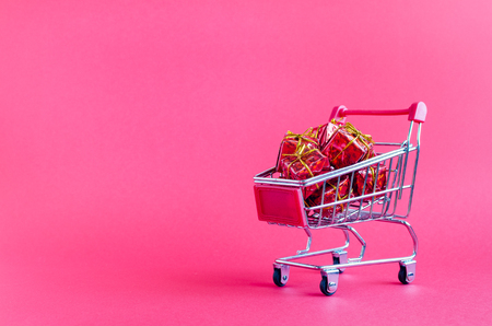 Small shopping cart with presents on pink background. Trolley from a supermarket full of red gift boxes. Online shopping concept Black Friday and Ciber Monday. Copy space. Foto de archivo - 121073262