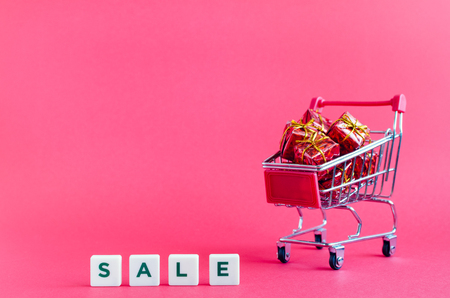 Small shopping cart with presents and word SALE on pink background. Trolley from a supermarket full of red gift boxes. Online shopping concept Black Friday and Ciber Monday. Copy space. Foto de archivo - 121073263
