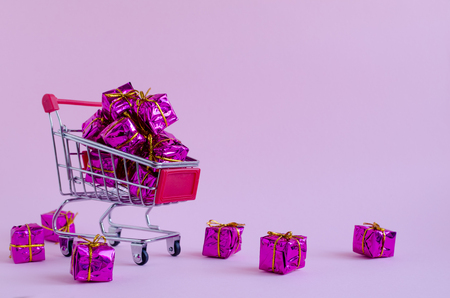 Small shopping cart with presents on pink background. Trolley from a supermarket full of purple gift boxes. Online shopping concept Black Friday and Ciber Monday. Copy space. Foto de archivo - 121073264