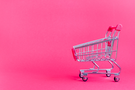 Small empty shopping cart on pink background. Trolley from a supermarket. Shopping concept Black Friday and Ciber Monday. Copy space. Foto de archivo - 121073271