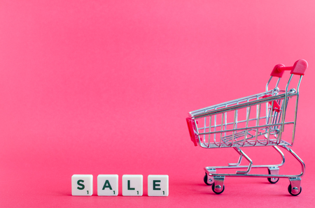 Empty grocery cart and word SALE on pink background. Trolley from a supermarket. Online shopping concept Black Friday and Ciber Monday. Copy space. Foto de archivo - 120870475