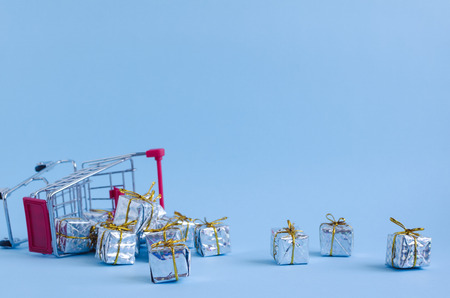 Overturned small shopping cart with presents on blue background. Trolley from a supermarket full of silver gift boxes. Online shopping concept Black Friday and Ciber Monday. Copy space. Foto de archivo - 120870473