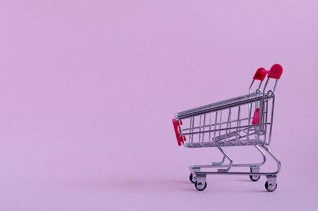 Small empty shopping cart on pink background. Trolley from a supermarket. Shopping concept Black Friday and Ciber Monday. Copy space. Foto de archivo - 120870477