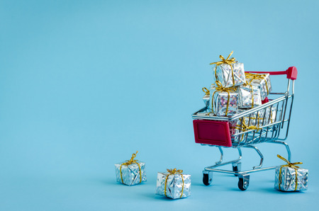 Small shopping cart with presents on blue background. Trolley from a supermarket full of silver gift boxes. Online shopping concept Black Friday and Ciber Monday. Copy space. Foto de archivo - 120870479