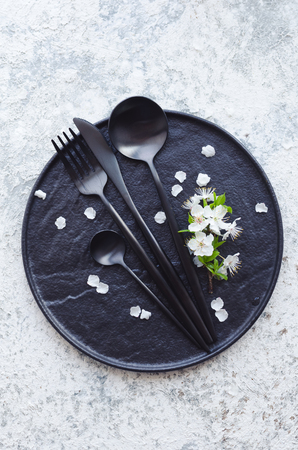 Spring table setting with white cherry blossom and cutlery on grey background. Mockup design layout for your text. Mothers Day concept. Copy space. Top view. Flat lay.