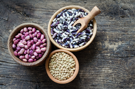 Assortment of dry organic beans and lentils in bowls on rustic wooden table. Balanced diet, cooking, vegetarian, raw and clean eating concept. Healthy food. Top view. Copy space. Foto de archivo