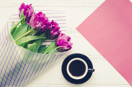 Cup of black coffee, bouquet of purple tulips and magenta paper texture on white wooden table. Top view. Copy space. Imagens