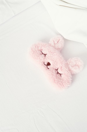 White bedding sheet, blanket and pillows with cute pink sleep mask on the bed. Rest, sleeping, comfort concept. Top view. Copy space. Stock Photo