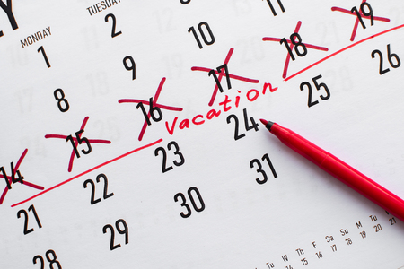 Vacation planning concept. Travel preparation: vacation plan written on calendar on white wooden table. Flat lay. Top view.