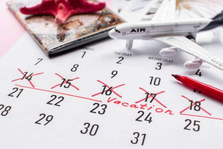 Vacation planning concept. Travel preparation: passport and vacation plan written on calendar on pink background. Stock Photo