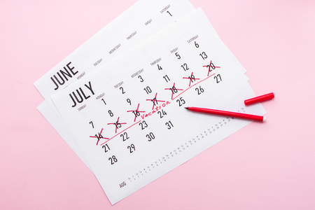 Vacation planning concept. Travel preparation: vacation plan written on calendar on pink background. Flat lay. Top view.