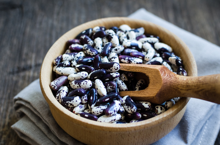 Dry organic purple grains-beens in a bowl on rustic wooden table. Haricot bean vegan protein source. Healthy food.