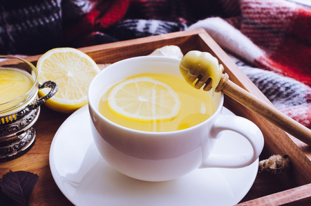 Healthy ginger tea with honey, ginger root and lemon on wooden tray with autumn fallen leaves on red warm woolen blanket. Hot drink for cold rainy days. Natural medicine against flu. Banco de Imagens