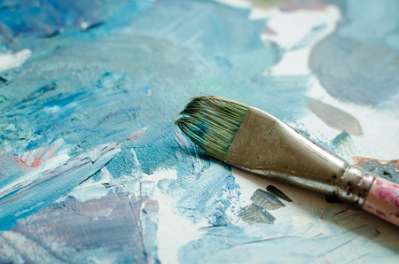 Artist paint brush on wooden palette. Texture mixed oil paints in different blue colors. Instruments tools for creative leisure. Painting hobby background. Paintings art concept. Copy space.