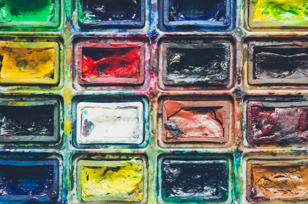 Closeup background texture of messy, used watercolor paintbox. Creative background. Paintings art concept. Painting hobby. Back to school. Top view. Copy space. Stok Fotoğraf
