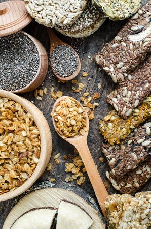 Healthy snacks. Dietary food. Sesame halva. Flakes, chia seeds in two bowls and spoons. Kozinaki, three energy bars and mint. The breadsticks with flax and sunflower seeds. Old wooden board. Top view.