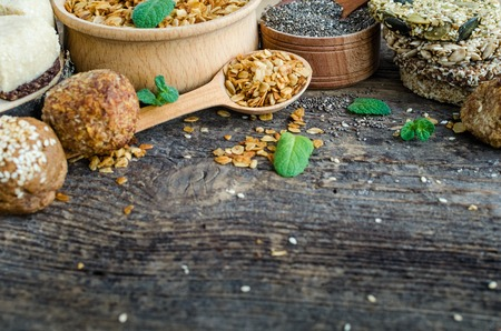 Healthy snacks. Fitness dietary food. Sesame halva. Flakes, chia seeds in two bowls and spoons. Kozinaki with sesame, peanuts, sunflower, pumpkin seeds. Dietary cookies. Old wooden board. Copy space. Stock Photo