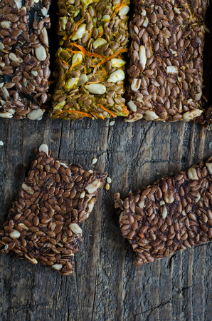 Fitness dietary food. Raw diet breadsticks with flax and sunflower seeds on rustic wooden board. Every product has filler with a mashrooms, carrot or algae. Vegan healthy nutrition concept. Top view. Stock Photo